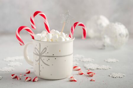 New Year or Christmas concept. Composition with marshmallows and candy canes on a gray concrete background.
