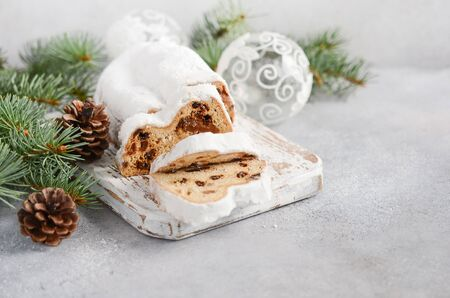 Christmas Stollen. Traditional German, European Festive Dessert. Holiday Concept Decorated with Fir Branches.