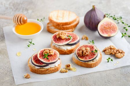 Bruschetta with fresh ricotta cheese, figs, nuts, thyme and honey on gray concrete background.