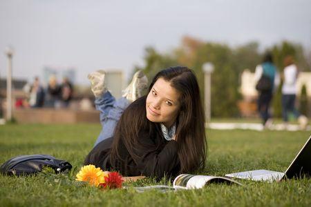 magazin: Chica con la revista y port�tiles en el c�sped, campus