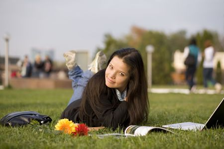 magazin: Girl with magazin and laptop on grass, campus