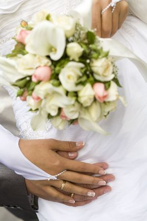 Ring & hands over white and flowers, wedding day photo