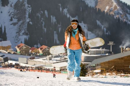 Lucky girl snowboarder in a mountain valley photo