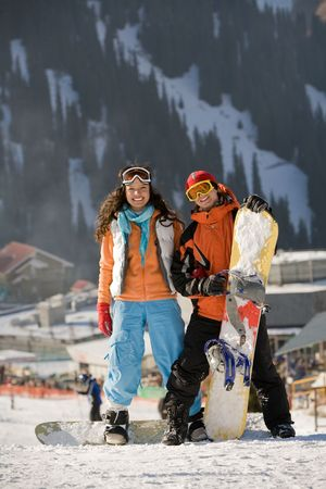 Lucky couple  snowboarders  in a mountain valley photo