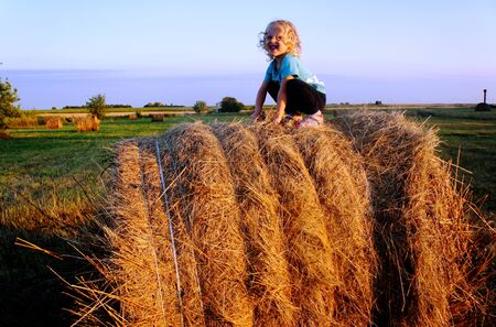 The curly, happy baby sits on hay