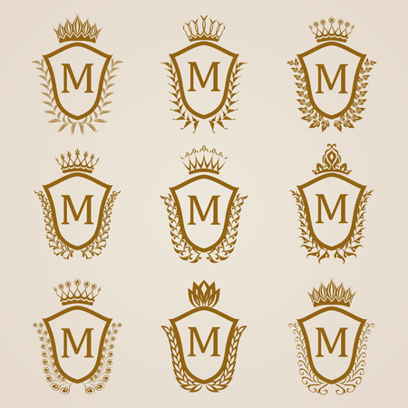 Set of luxury golden shields with laurel wreaths, crowns. Royal heraldic elements, emblems, icons, symbols, labels, badges, blazons, monograms for web, page design.