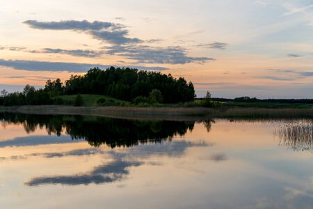 landscape of lake, orange and blue cloudy sky in Lithuania