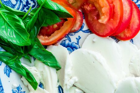 sliced tomatoes, basil and sliced mozzarella in blue plate closeup 版權商用圖片