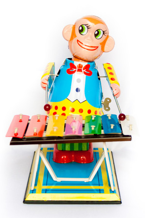 vivid tin toy  wind up monkey musician retouched and isolated on white background photo