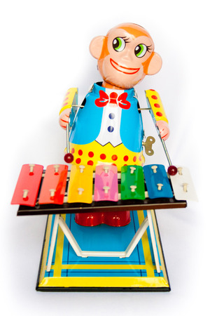 retouched: vivid tin toy  wind up monkey musician retouched and isolated on white background