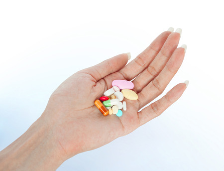 variety tablets on female hand retouched and isolated on smooth shadow background Banque d'images