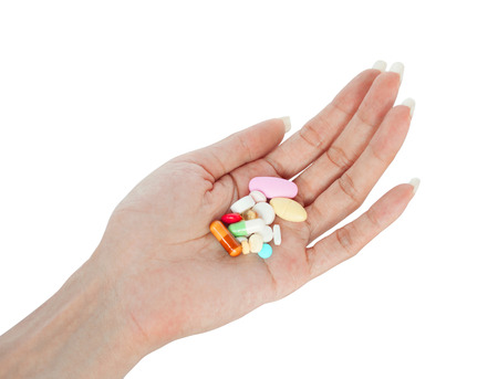 retouched: variety tablets on female hand retouched and isolated on white background