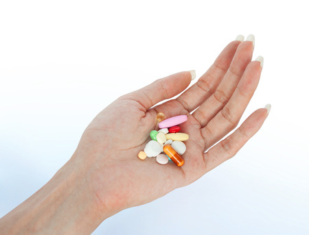 variety vitamins on female hand retouched and isolated on smooth shadow background Banque d'images