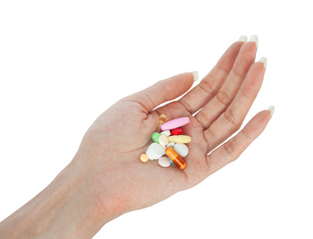 variety vitamins on female hand retouched and isolated on white background