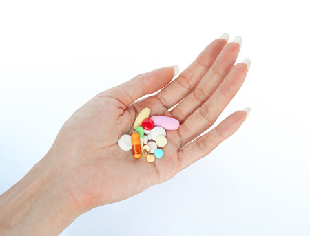 variety medicines on female hand retouched and isolated on smooth shadow background