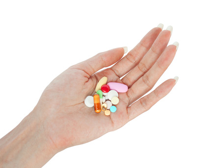 variety medicines on female hand retouched and isolated on white background