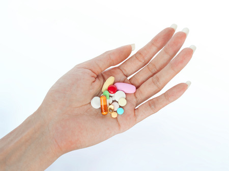 variety pills on female hand retouched and isolated on smooth shadow background