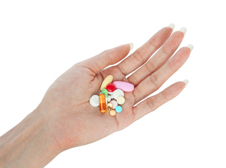 variety pills on female hand retouched and isolated on white background Banque d'images