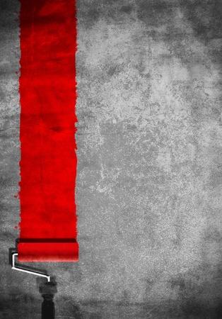 pintor de casas: rodillo de pintar con pintura roja en la pared blanca