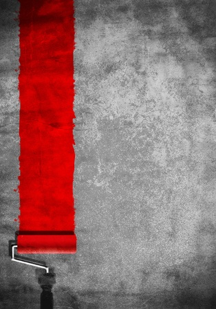 paint roller with red paint on white wall Stockfoto