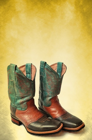 Dirty rodeo old boots leather on vintage background background photo