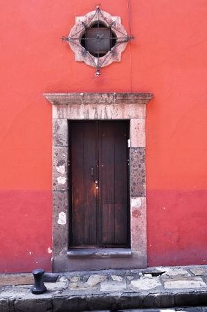 oldened: Front of an old mexican house - Colonial style door and window - San Miguel de Allende Mexico Stock Photo