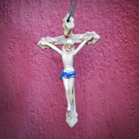 catholicism: Ceramic crucifix on a pink background