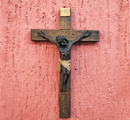 catholicism: Wood crucifix on a pink background