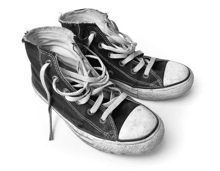 Oude zwarte sneakers op een witte achtergrond Stockfoto