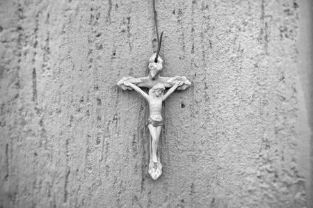 catholicism: Gray scale Ceramic crucifix on a cement wall