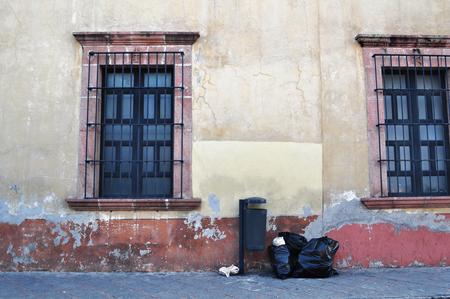 casa colonial: Frente a una vieja casa mexicana con el bote de basura y bolsas de basura - ventanas de estilo colonial - Querétaro se México