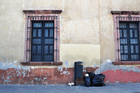 colonial house: Front of an old mexican house with trash can and garbage bags - Colonial style windows - Queretato Mexico