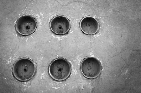 electric line: Line up of six electric power meters on vintage wall, black and white scene