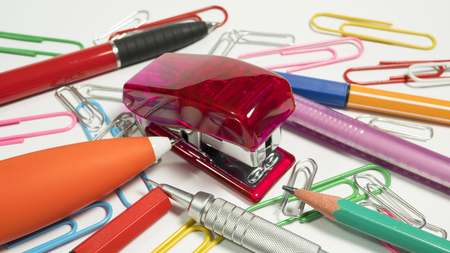 Office and school supplies, colorful objects placed on a white background.