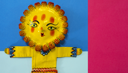 Mexican handicraft, hand painted doll representing the sun, on a colorful paper background. Stock Photo