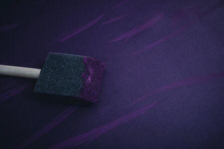 Sponge Brush on Canvas Applying purple paint.