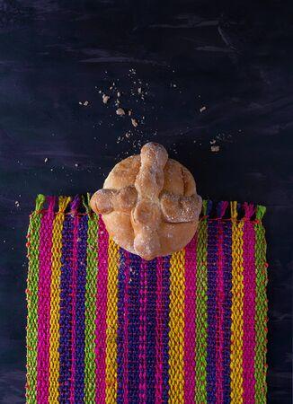 Pan de Muerto, Bread of Dead Mexican Sugar Scone on Woven Tablecloth.