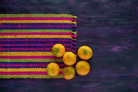 Mandarin Orange Tangerines Fresh Fruit on Woven Tablecloth.