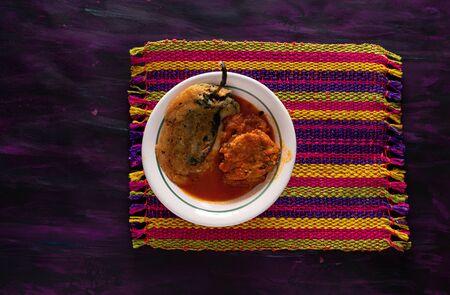 Chile Relleno and Caldillo Mexican food dish on Woven Tablecloth. Stock Photo
