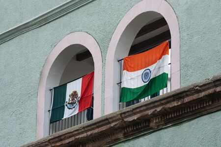 Flags of Mexico and India placed on the facade of a Mexican house.