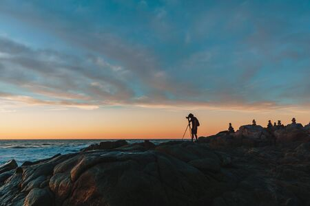 Photographer on Cliff and Beautiful Sunset in Mexican beach.