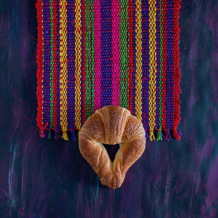 Mexican Cuernito Bread, Sugar Croissant on Woven Tablecloth.