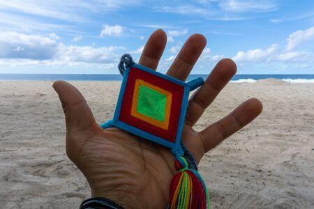 Hand Holding Mandala Eye of God Mexican Huichol Crafts in Sayulita Beach.