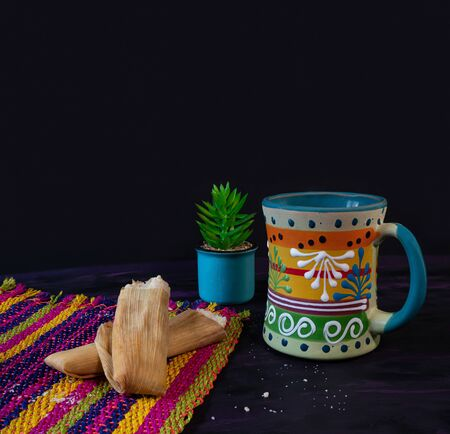 Tamales Mexican dish made of Corn dough and Coffee Jar on Woven Tablecloth.