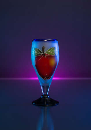 Blown Class Cup with an hand painted apple on dark background and light. Stockfoto
