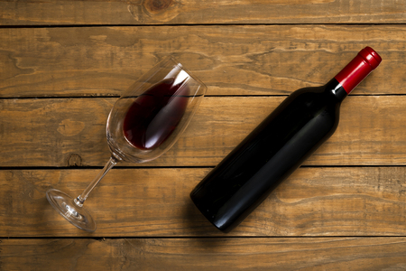 Bottle of wine and glass on wooden background. Top view with copy space.