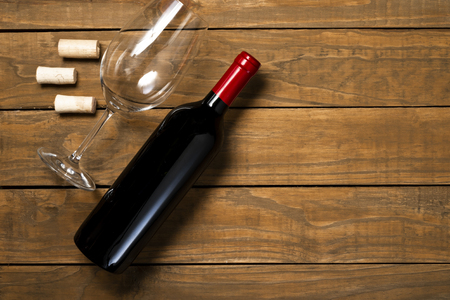 Bottle of wine glass and corks on wooden background. Top view with copy space. 免版税图像