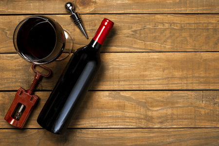 Bottle of wine glass and corkscrew on wooden background. Top view with copy space.