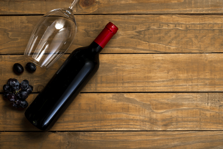 Bottle of wine and glass and grapes on wooden background. Top view with copy space. 免版税图像