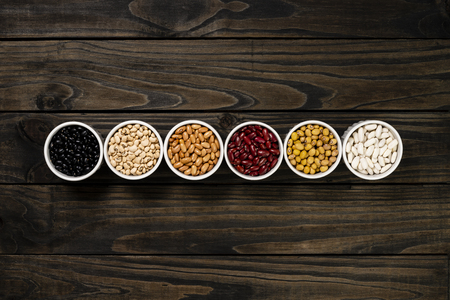 Assortment of beans in a pot. Wooden black background.